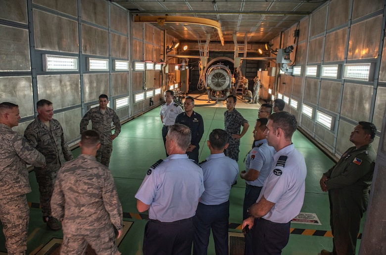 U.S. Air Force Tech Sgt. Travis Arrona, 18th Component Maintenance Squadron, briefs officers of allied and partner nations about aircraft engine maintenance and testing during the 2018 Fighter Logistics and Safety Symposium Aug. 21, 2018, at Kadena Air Base, Japan. The symposium enabled air force officers from Australia, Indonesia, Japan, the Philippines, Singapore and Thailand to visit fighter support units assigned to the 18th Wing and interact with Airmen who support the fighter mission. (U.S. Air Force photo by Staff Sgt. Micaiah Anthony)