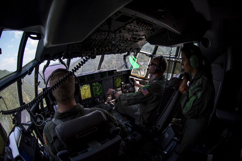 U.S. Air Force Capt. Bryant Bailey, 37th Airlift Squadron pilot, and Lt. Col. Alex Miller, 37th AS director of operations, fly a C-130J Super Hercules aircraft over Romania as Romanian air force Lt. Cmdr. Nicoleta Udrescu, Air Base 90 Otopeni pilot, watches during exercise Carpathian Summer 2018, Aug. 21, 2018. The purpose of the bilateral training exercise is to enhance interoperability and readiness by conducting combined air operations with the Romanian air force. (U.S. Air Force photo by Senior Airman Devin Boyer)