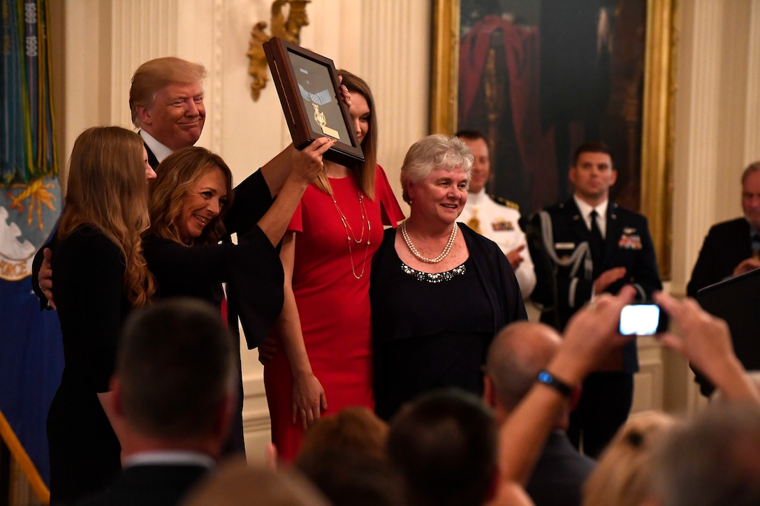 Valerie Nessel, the spouse of Tech. Sgt. John Chapman, holds up the Medal of Honor after receiving it from President Donald J. Trump during a ceremony at the White House in Washington, D.C., Aug. 22, 2018. Chapman was posthumously awarded the Medal of Honor for actions on Takur Ghar mountain in Afghanistan March 4, 2002. His elite special operations team was ambushed by the enemy and came under heavy fire from multiple directions. Chapman immediately charged an enemy bunker through thigh-deep snow and killed all enemy occupants. Courageously moving from cover to assault a second machine gun bunker, he was injured by enemy fire. Despite severe wounds, he fought relentlessly, sustaining a violent engagement with multiple enemy personnel before making the ultimate sacrifice. With his last actions he saved the lives of his teammates. (U.S. Air Force photo by Staff Sgt. Rusty Frank)