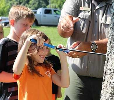 Campers use an increment corer to uncover the life history of a tree July 26, 2018 at Cordell Hull Lake in Carthage, Tenn. (USACE Photo by Ashley Webster)