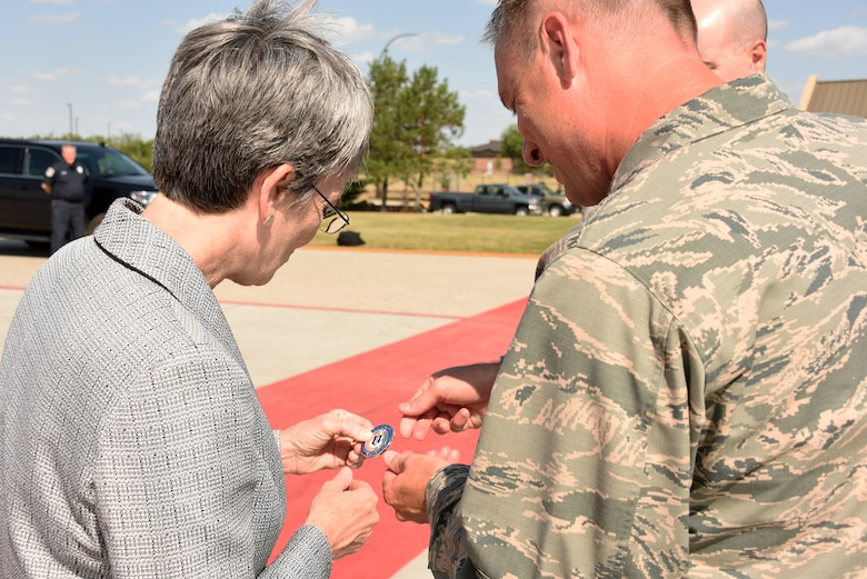 Secretary of the Air Force Heather Wilson admires a coin Col. Benjamin Spencer gave to her August 21, 2018, on Grand Forks Air Force Base, North Dakota. Wilson visited the base for a tour August 20, and had the chance to meet several Airmen across multiple squadrons to speak to them and award them with a coin herself. (U.S. Air Force photo by Airman 1st Class Elora J. Martinez)