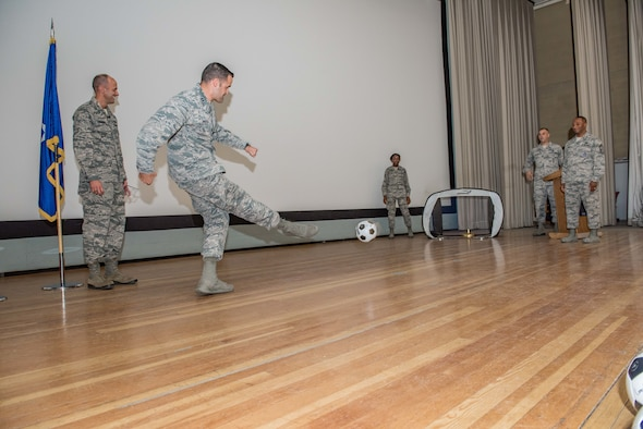 Capt. Matthew Spurgeon kicks a soccer ball into a portable goal during a 412th Test Wing commander's call and second quarter awards ceremony held in the base theater Aug. 23. (U.S. Air Force photo by Matt Williams)
