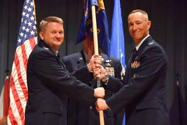 U.S. Air Force Col. Max Pearson, 480th Intelligence, Surveillance and Reconnaissance Wing commander, hands the 480th ISR Group's guidion to new commander, Col. Abraham Jackson during the change of command ceremony Aug. 15, 2018, at Fort Gordon, Ga.