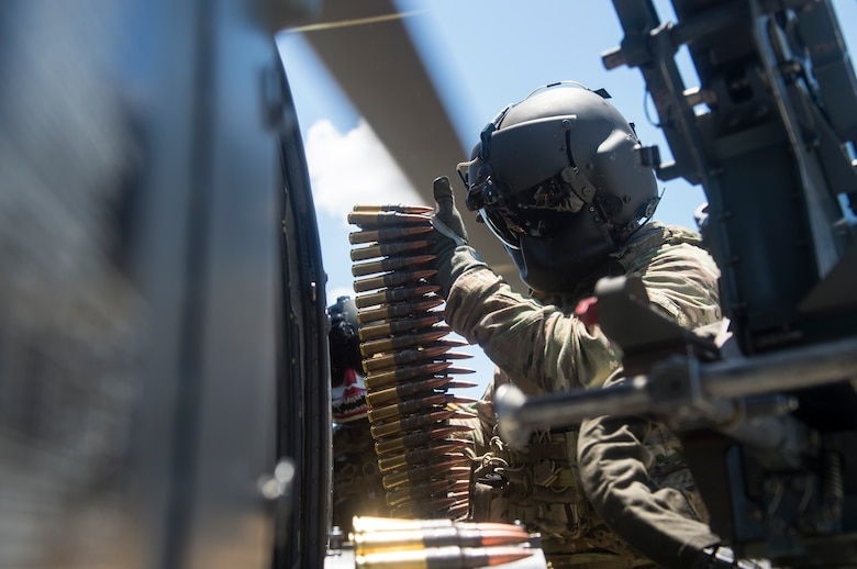 Special missions aviators from the 41st Rescue Squadron (RQS) load ammunition into an M2 machine gun mounted to an HH-60G Pave Hawk, Aug. 17, 2018, at Patrick Air Force Base, Fla. Airmen from the 41st RQS and 41st Helicopter Maintenance Unit traveled to Patrick AFB to participate in a spin-up exercise. During the exercise, Airmen faced scenarios and situations they may encounter downrange. (U.S. Air Force photo by Senior Airman Janiqua P. Robinson)