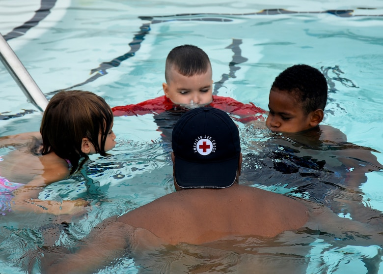 Bobby Broome, Joint Base Andrews pool manager and aquatics director, teaches kids how to submerge their faces during a water safety camp at Joint Base Andrews, Md., Aug. 21, 2018. Camp participants learned the basics of swimming as well as water safety and life-saving techniques. (U.S. Air Force photo by Senior Airman Abby L. Richardson)