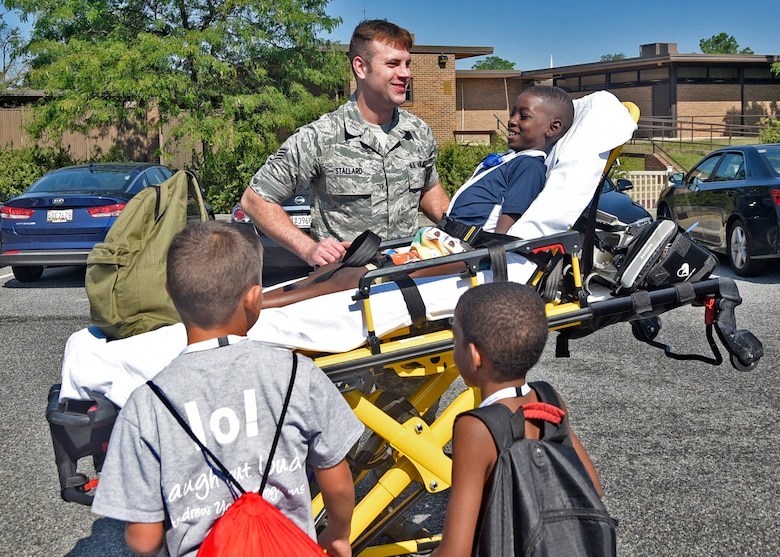 Staff Sgt. Troy Stallard, 11th Medical Operations Squadron paramedic, demonstrates how to use a stretcher during the third annual water safety camp at Joint Base Andrews, Md., Aug. 23, 2018. Camp participants met with representatives from security forces, the fire department, emergency services and the Red Cross to teach them about what first responders do in an emergency. (U.S. Air Force photo by Senior Airman Abby L. Richardson)