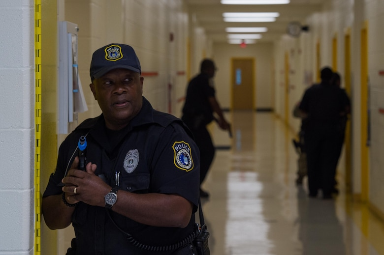 A 733rd Security Forces Squadron officer keeps watch as other officers clear rooms during a school violence exercise at Joint Base Langley-Eustis, Virginia, Aug. 23, 2018.