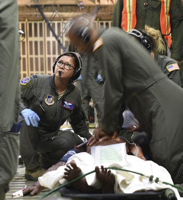 Staff Sgt. Jamal Wardlaw, 59th Medical Wing cardio pulmonary technician, Joint Base San Antonio, Texas, center, performs cardio pulmonary resuscitation on a simulated patient Aug. 23 at Travis Air Force Base, Calif., during an exercise testing the C-5M Super Galaxy's ability to function as an aeromedical evacuation transport vessel. The. U.S. Air Force currently does not utilize the C-5M cargo compartments for AE flights and is using the exercise as a way to test the aircraft's capability during a large-scale global response. (U.S. Air Force photo by Staff Sgt. Amber Carter)
