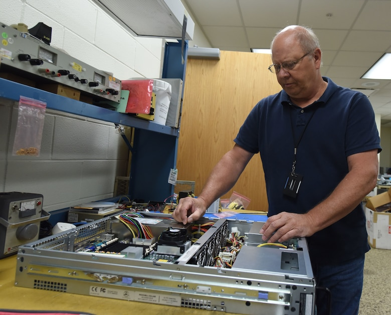 Randy Mack, a B-1 simulator maintenance technician, works on a piece of computer equipment at Ellsworth Air Force Base, S.D., Aug. 21, 2018. The B-1 simulator is a state-of-the-art facility, which is powered by multiple computers so it can display images and allow aircrew members to complete realistic training scenarios. (U.S. Air Force photo by Airman 1st Class Thomas Karol)