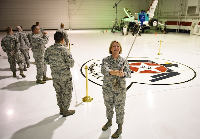 Chief Master Sgt. Kathleen McCool, 53rd Wing command chief at Eglin Air Force Base, Florida, takes a picture in the Thunderbirds hangar during a tour with the Warrior Stripe program at Nellis Air Force Base, Nevada, Aug. 18, 2018. The two-week course brought together 40 U.S. Air Force Warfare Center NCOs to provide an avenue for them to develop as military and professional leaders. (U.S. Air Force photo by Airman 1st Class Andrew D. Sarver)