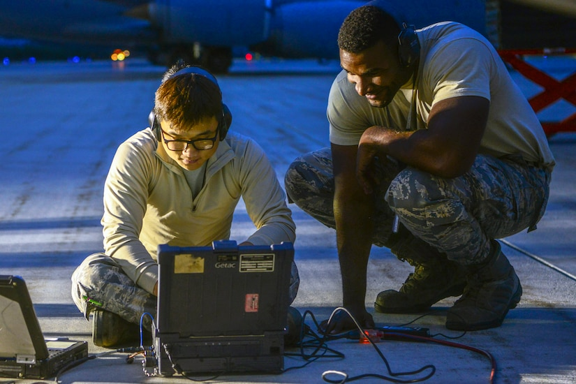 Two airmen read a computer screen together.