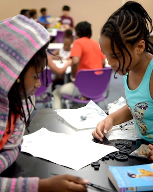 Zariah Dunn and Nia Jackson, students at the Center of Innovation asses' instructions before building a solar panel toy car at the Youth Center on Joint Base Andrews, Md., July 6, 2018. The COI was transformed in 2015 after receiving funding from the Boys and Girls Club of America and Raytheon to accommodate lessons in science, technology, engineering and math.