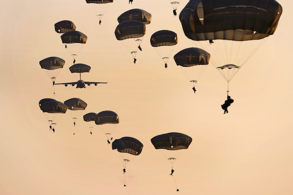 Soldiers descend after jumping from an Air Force C-17 Globemaster aircraft.