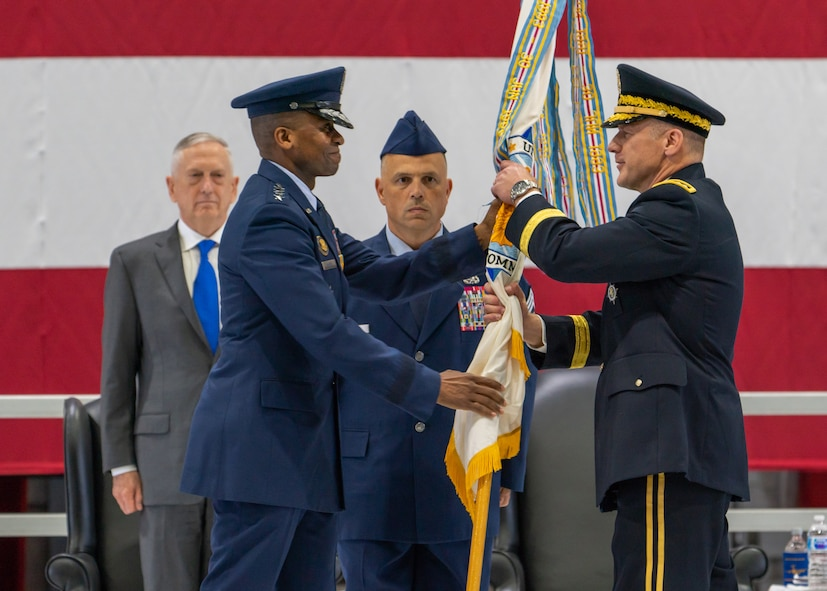 U.S. Air Force Gen. Darren W. McDew passes the U.S. Transportation Command guidon to U.S. Army Gen. Stephen R. Lyons during a change of command ceremony held Aug. 24, 2018, at Scott Air Force Base, Illinois.