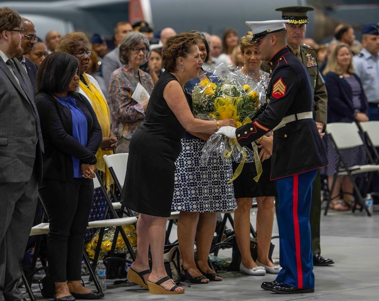 U. S. Marine Sgt. Joel Gonzalez presents a bouquet of yellow roses to Mrs. Maureen Lyons on behalf of the men and women of U.S. Transportation Command.