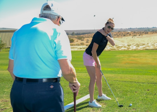 Air Force retiree Lawrence Davis receives golfing tips from professional golfer Molly Aronsson, during a golf clinic at Muroc Lake Golf Course on Edwards Air Force Base Aug. 24. (U.S Air Force photo by Giancarlo Casem)