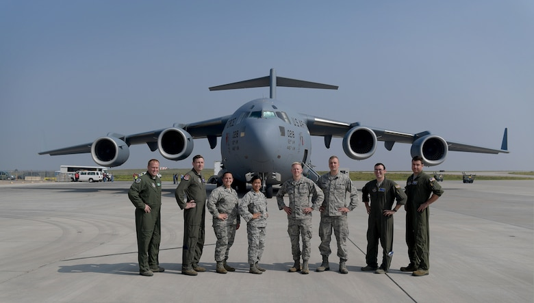 Airmen involved in the loading of the very first GPS III satellite gather for a group photo in front of a C-17 Globemaster III prior to its takeoff from Buckley Air Force Base, Colorado, Aug. 20, 2018.