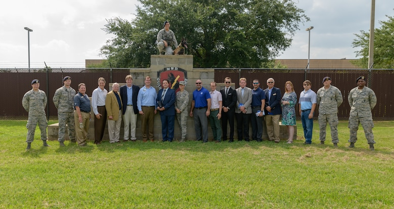 U.S. Air Force Col. Marcia Quigley, 81st Mission Support commander and 81st Security Forces Squadron personnel pose for a group photo with honorary commanders during the 81st Mission Support Group Honorary Commanders tour at the MWD Kennels at Keesler Air Force Base, Mississippi, Aug. 23, 2018. The honorary commander program is a partnership between base leadership and local civic leaders to promote strong ties between military and civilian leaders. (U.S. Air Force Photo by Andre' Askew)
