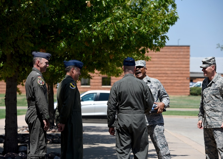 Senior leadership of the 80th FTW and CMSgt. Jack Johnson Jr. share a laugh outside their headquarters building.