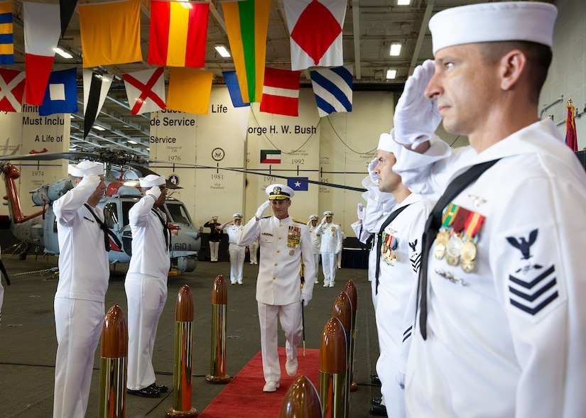 Navy Vice Adm. Andrew Lewis salutes as he arrives to the U.S. 2nd Fleet establishment ceremony aboard the nuclear aircraft carrier USS George H.W. Bush in Norfolk, Va.