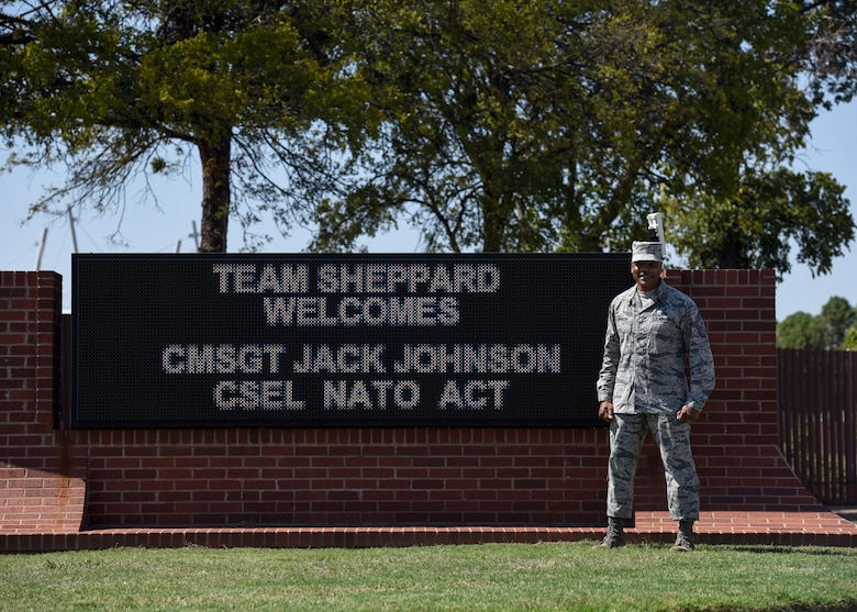 CMSgt. Jack Johnson Jr. stands in front of an electronic welcome sign made for him in front of Sheppard Air Force Base.