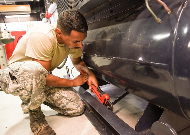 Senior Airman Edgar Pacheco, a powered system support mechanic with the 162nd Maintenance Squadron Aerospace Ground Equipment Flight, turns a wrench on an MB-8 building compressor, as he performs a hydrostatic test on the equipment. The equipment requires this specialized testing every five years, which consists of pumping water into the tank to determine if it can hold pressure.
