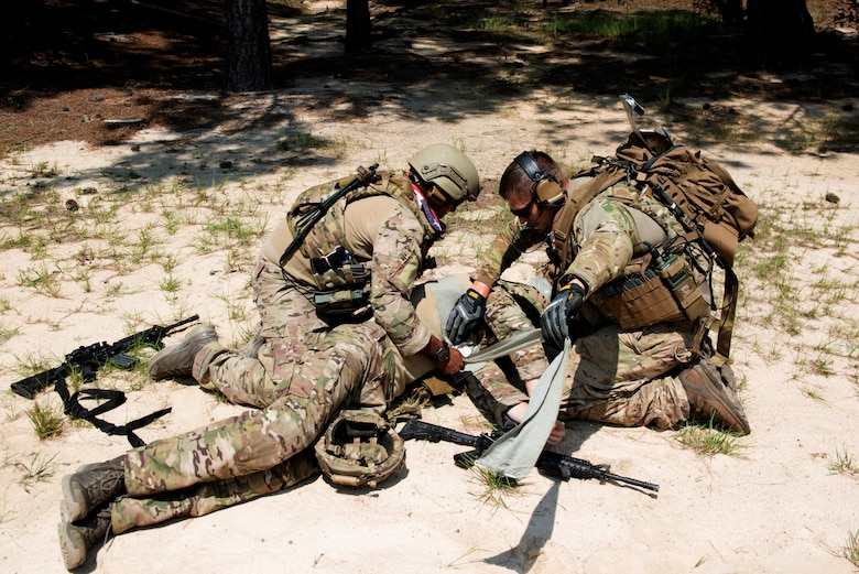 U.S. Air Force Senior Airman Elias Omar, 20th Civil Engineer Squadron (CES) explosive ordnance disposal (EOD) journeyman, left, and Staff Sgt. Wesley Clayton, 20th CES EOD craftsman, right, simulate life-saving treatment to Airman 1st Class Evan Cooling, 20th CES EOD apprentice, at McCrady Army National Guard Base training area near Columbia, S.C., Aug. 23, 2018.