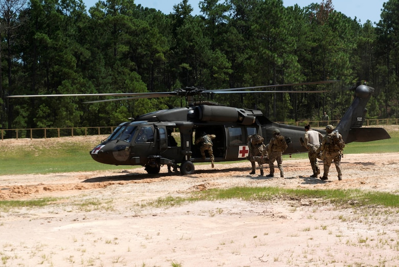 U.S. Air Force Airmen assigned to the 20th Civil Engineer Squadron explosive ordnance disposal flight carry simulated patients into a UH-60 Black Hawk helicopter assigned to McEntire Joint National Guard Base, S.C., at McCrady Army National Guard Base training area near Columbia, S.C., Aug. 23, 2018.