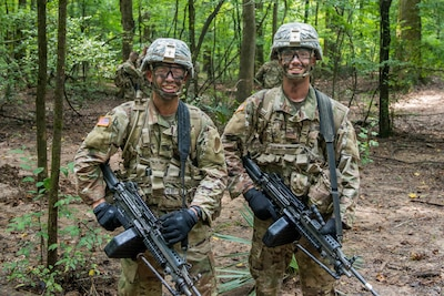 Two soldiers wearing camouflage paint stand in a forest.