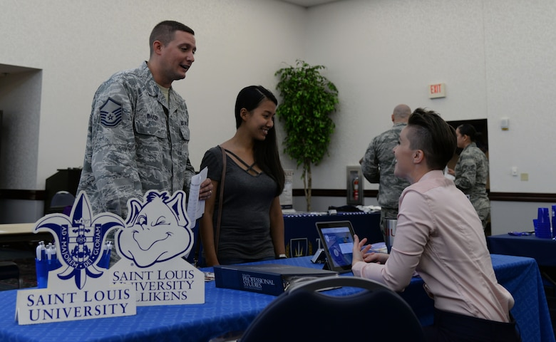 Master Sgt. Scott Baker, 18th Air Force, talks to a representative from Saint Louis University at the Education Fair on Aug. 16, 2018 at the Scott Air Force Base Events Center on Scott AFB, Ill. Representatives from over 40 Colleges, universities, and education support agencies attended the fair to give participants an opportunity to compare educational opportunities.