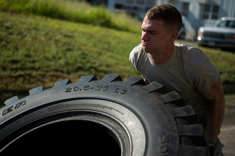 U.S. Air Force Staff Sgt. Anthony Zygmunt, 7th Reconnaissance Squadron alarm monitor, flips a tire during a physical training test as part of Air Combat Command's Defender Challenge team selection at Joint Base Langley-Eustis, Virginia, Aug. 24, 2018.