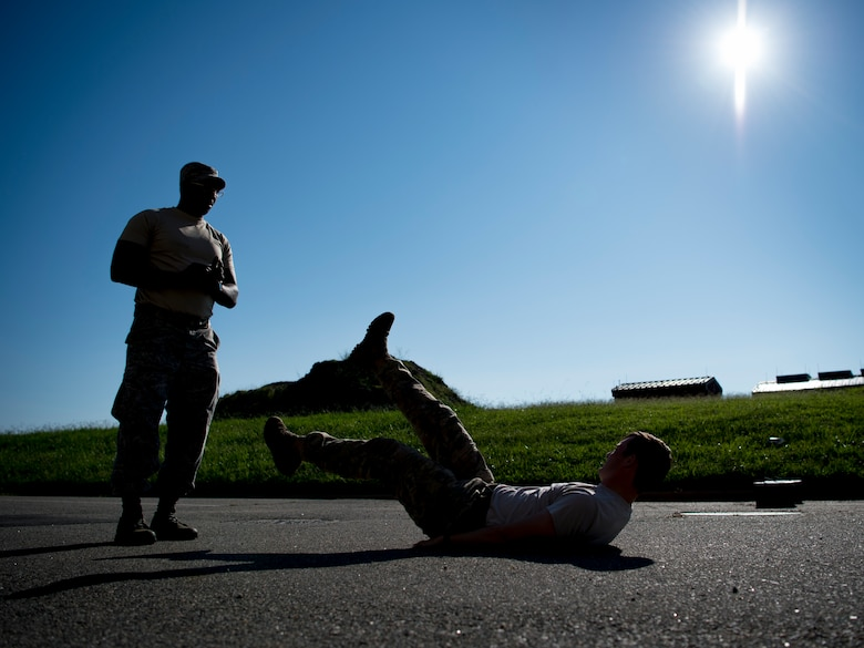U.S. Air Force Tech. Sgt. Alexis Rice, Air Combat Command Directorate of Logistics, Engineering and Force Protection NCO in charge of mission assurance, watches Senior Airman Jeffrey Lewis, 822nd Base Defense Squadron fire team leader, perform flutter kicks during a physical training test as part of Air Combat Command's Defender Challenge team selection at Joint Base Langley-Eustis, Virginia, Aug. 24, 2018