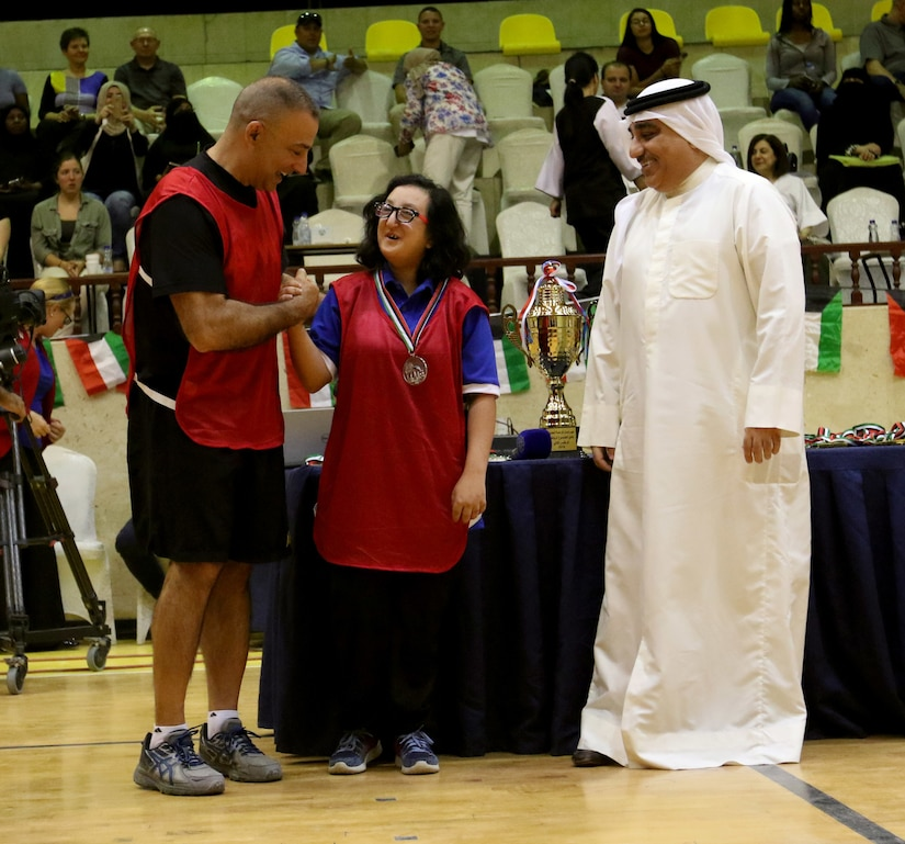 Brig. Gen. Mark McCormack, deputy division commander – support, 28th Infantry Division/Task Force Spartan, presents a medal and congratulates one of the participants from Special Olympics-Kuwait after the sports night at Aridiyah Youth Center, Kuwait. McCormack and other Soldiers from Task Force Spartan joined together with the sports club to compete in several sports.