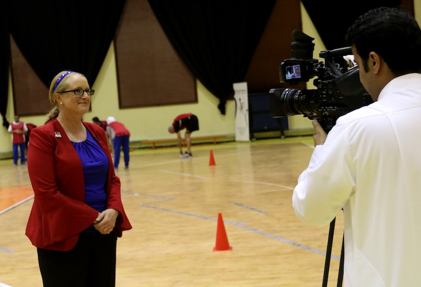 Maj. Amanda Harrah, deputy civil affairs officer for the 28th Infantry Division, Task Force Spartan, talks with a Kuwaiti reporter about TFS Soldiers joining together with the Special Olympics-Kuwait to play several different sports at Aridiyah Youth Center, Kuwait.