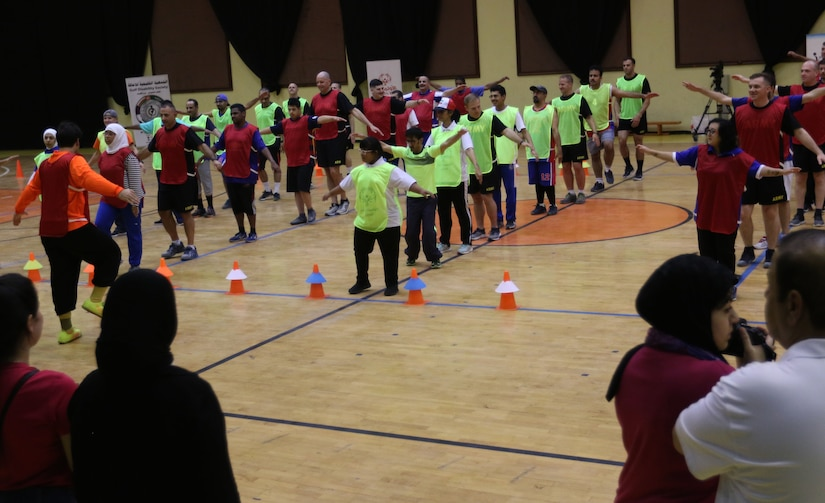 Soldiers from Task Force Spartan and athletes with the Special Olympics-Kuwait perform some warm-up drills and stretching in preparation for the sports events at Aridiyah Youth Center, Kuwait.