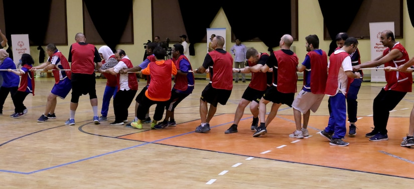Task Force Spartan Soldiers and athletes with the Special Olympics-Kuwait unite for the tug-of-war portion of the sports night at Aridiyah Youth Center, Kuwait. Both teams were comprised of a mix of Soldiers and club athletes who united in their enjoyment of sports.
