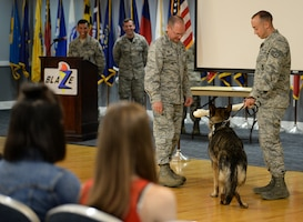Col. Gary Hayward, 14th Mission Support Group commander, presents Military Working Dog Cherry, 14th Security Forces Squadron, a gift during her retirement ceremony Aug. 24, 2018, on Columbus Air Force Base, Mississippi, while her handler, Staff Sgt. Nicholas Heckler, former 14th SFS MWD handler, looks on. Cherry was assigned to the 14th Security Forces Squadron, faithfully serving 10 years in the U.S. Air Force. (U.S. Air Force photo by Airman Hannah Bean)