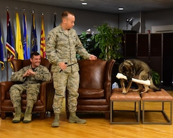 Staff Sgt. Nicholas Heckler, former 14th Security Forces Squadron military working dog handler, prepares to walk with newly retired MWD Cherry, during her retirement ceremony Aug. 24, 2018, on Columbus Air Force Base, Mississippi. Cherry retired after serving the Air Force for 10 years, and will go on to live with Heckler. (U.S. Air Force photo by Elizabeth Owens)