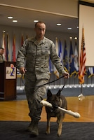 Staff Sgt. Nicholas Heckler, former 14th Security Forces Squadron military working dog handler, walks with newly retired MWD Cherry, during her retirement ceremony Aug. 24, 2018, on Columbus Air Force Base, Mississippi. Cherry retired after serving the Air Force for 10 years Cherry as an explosive detector dog. (U.S. Air Force photo by Airman 1st Class Keith Holcomb)