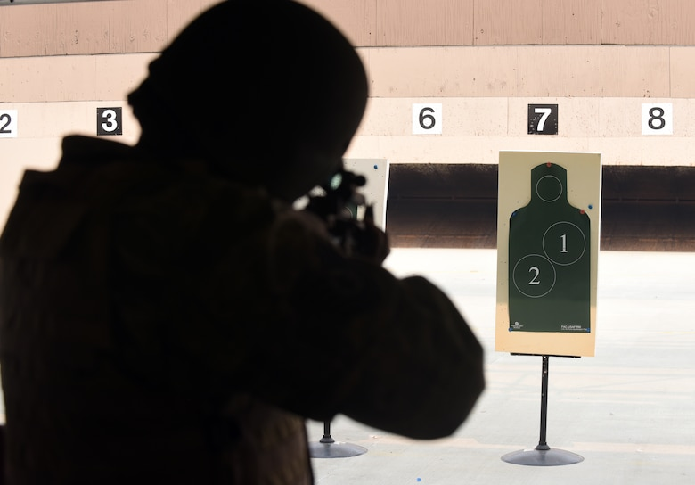 An Airmen points his M4 rifle at his target during a qualifying course