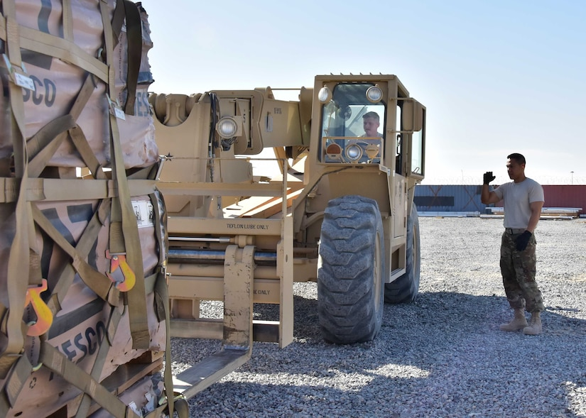 Air Force Master Sgt. Allan Reeves, Joint Special Operations Forces Support Detachment-K noncommissioned officer in charge of movements, guides Air Force Staff Sgt. Christopher Jensen, JSSD-K assistant NCOIC in charge of movements, as he uses a Skytrak 10K vertical reach forklift to move a pallet of Hesco barriers at an undisclosed location in Southwest Asia.