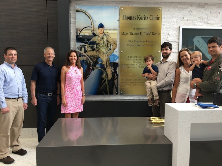 """The Koritz family shown in front of the memorial wall at the new Thomas Koritz Clinic, Seymour Johnson Air Force Base, North Carolina. The U.S. Army Corps of Engineers oversaw the construction of the $55 million facility which was named in honor of Air Force Maj. Thomas F. """"Teek"""" Koritz, a flight surgeon and pilot killed in a bombing mission during the Gulf War. (Courtesy photo)"""