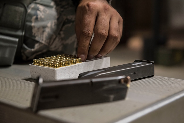 A U.S. Airman grabs a round to load into an M9 pistol magazine at the firing range on Shaw Air Force Base (AFB), S.C., Aug. 22, 2018.