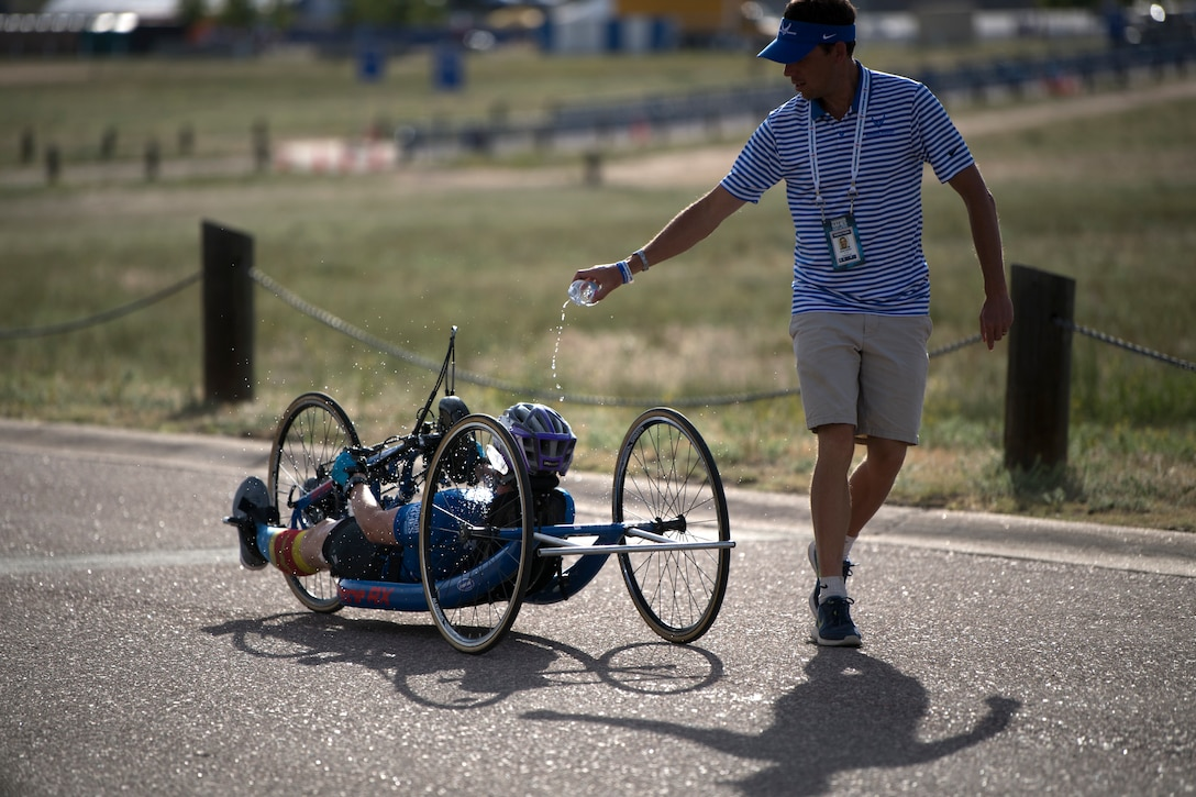 Air Force Coach Aaron Moffett pours water over Master Sgt. Lisa Goad, Team Air Force athlete, during the 2018 DoD Warrior Games cycling competition at the U.S. Air Force Academy in Colorado Springs, Colo. on June 6, 2018. (DoD photo by EJ Hersom)