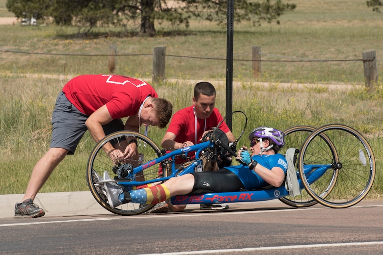 Master Sgt. Lisa Goad, Team Air Force athlete, observes as her bike is fixed after a crash during a hand-cycling race as part of the 2018 DoD Warrior Games at the U.S. Air Force Academy in Colorado Springs, Colo. on June 6. The Warrior Games are an annual event, established in 2010, to introduce wounded, ill and injured service members to adaptive sports as a way to enhance their recovery and rehabilitation. (DoD Photo by Roger L. Wollenberg)