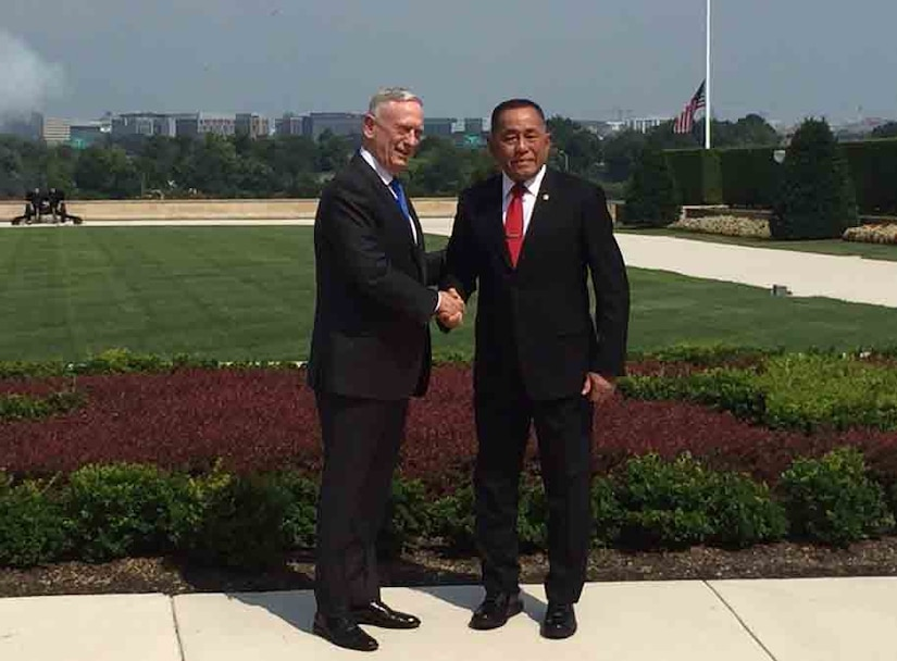 Defense secretary shakes hands with Indonesian defense minister.