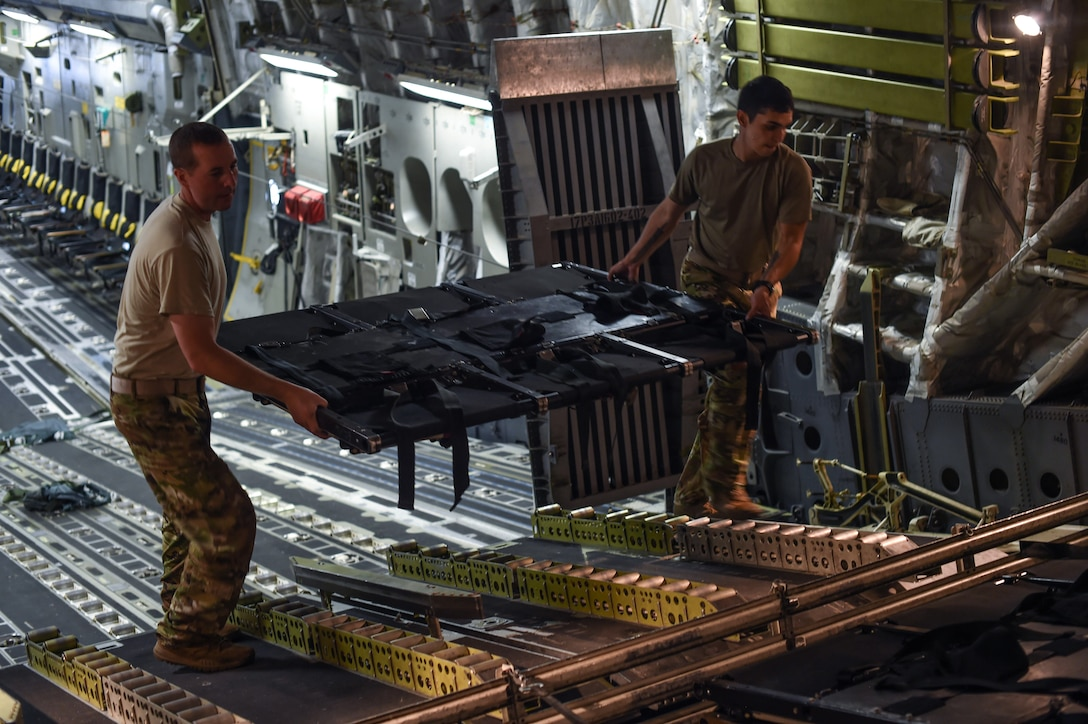 U.S. Air Force Tech. Sgt. Drew Czarnecki, left, and Staff Sgt. Raymond Sandoval, both 7th Airlift Squadron loadmasters, stow the disassembled part of seat away inside a C-17 Globemaster III during Exercise Predictable Iron at Pope Field, N.C., Aug. 23, 2018. Over the course of three days, Czarnecki, Sandoval and other Airmen helped drop 1,005 paratroopers during the exercise.  (U.S. Air Force photo by Senior Airman Tryphena Mayhugh)