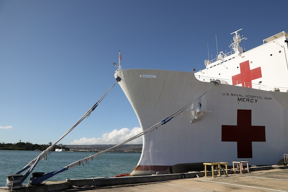 The USNS Mercy, docked alongside the USS Arizona Memorial July 9, 2018, on Joint Base Pearl Harbor – Hickam is a hospital ship that provides various medical services in the event of crisis. Of interest to members of the 446th Aeromedical Squadron are not only capabilities but how patient movement is accomplished. (U.S. Air Force photo by David L. Yost)