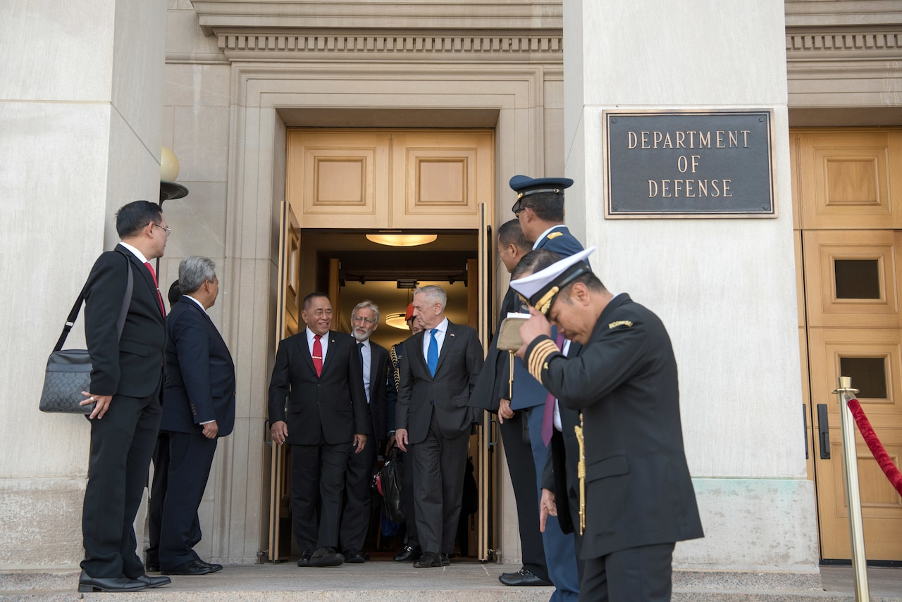 Defense Secretary James N. Mattis walks out of the Pentagon with several officials.