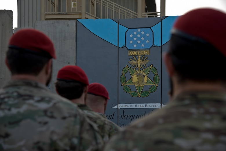 Members of the Special Operations Community gather in front of a mural during the Medal of Honor ceremony for U.S. Air Force Master Sgt. John Chapman on Bagram Airfield, Afghanistan, August 28, 2018. The mural was painted in memory of Chapman for his heroic actions during the Battle of Takur Ghar. (U.S. Air Force photo by Staff Sgt. Kristin High)